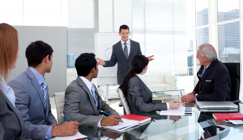 Confident-businessman-giving-a-presentation-to-his-team-in-the-office-